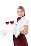Waitress. Young waitress carrying a tray with glasses of wine on a white background Royalty Free Stock Photos