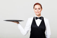 Waitress. Pretty waitress with an empty tray Royalty Free Stock Image