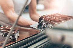 Waitress arranging cake at display cabinet Royalty Free Stock Photography
