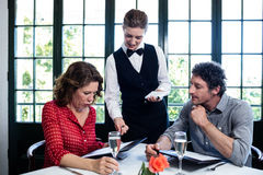 Waitress assisting a couple while selecting menu Royalty Free Stock Images