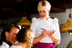 Waitress in Bavarian restaurant taking orders Royalty Free Stock Photo