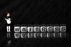 Waitress on beads with a scale model waiter standing next to word. On wooden background royalty free stock photos