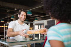 Waitress behind the counter giving loaf to customer Royalty Free Stock Photos
