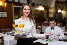 Waitress with beverages. Smiling nippy serving bar guests with the beverages Royalty Free Stock Image