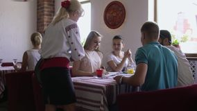 Waitress bring drinks to studying students in cafe stock footage