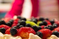 Waitress Bringing Desert. A waitress in a restaurant bringing a pavlova desert to the table Stock Photography
