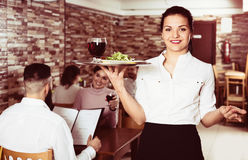 Waitress bringing order for guests in country cafe Royalty Free Stock Photos