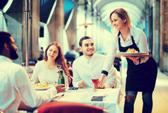 Waitress bringing order at terrace table in summer day Stock Images