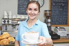 Waitress In Cafe Serving Customer With Coffee. Portrait Of Waitress In Cafe Serving Customer With Coffee Royalty Free Stock Images