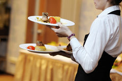 Waitress carrying three plates with meat dish. Waitress is carrying three plates with meat dish stock image