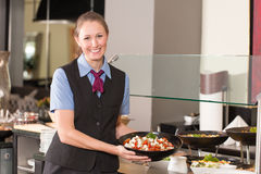 Waitress or catering professional putting food into buffet. Waitress or catering professional putting food into a buffet Royalty Free Stock Photo