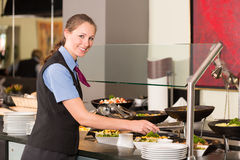 Waitress or catering professional putting food into buffet Royalty Free Stock Photos