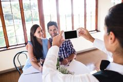 Waitress clicking photo of a couple in restaurant. Waitress clicking photo of a young couple in restaurant royalty free stock images