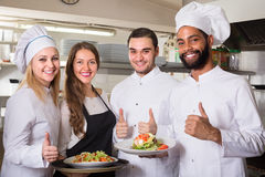 Waitress and cooking team at kitchen. Positive waitress and cooking team at professional kitchen in restaurant stock images
