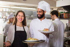 Waitress and cooking team at kitchen. Smiling waitress and cooking team at professional kitchen in restaurant royalty free stock image