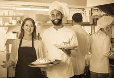 Waitress and cooking team in restaurant. Happy young waitress and cooking team at professional kitchen in restaurant royalty free stock photos