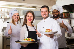 Waitress and cooking team in restaurant Stock Photos