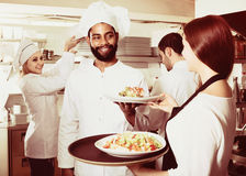 Waitress and cooking team in restaurant. Smiling waitress and cooking team at professional kitchen in restaurant royalty free stock images