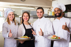 Waitress and cooking team in restaurant. Smiling young waitress and cooking team at professional kitchen in restaurant royalty free stock photography