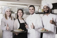 Waitress and cooking team in restaurant. Smiling young waitress and cooking team at professional kitchen in restaurant stock photography