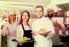 Waitress and crew of professional cooks posing at restaurant Royalty Free Stock Photos