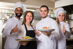 Waitress and crew of professional cooks posing at restaurant Stock Photos