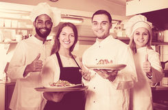 Waitress and crew of professional cooks posing at restaurant Stock Image