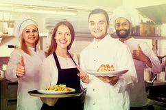 Waitress and crew of professional cooks posing at restaurant. Happy waitress and crew of professional cooks posing at restaurant kitchen royalty free stock images