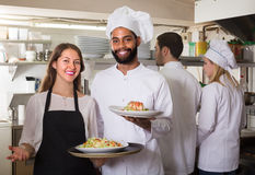 Waitress and crew of professional cooks posing at restaurant Stock Images