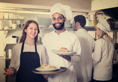 Waitress and crew of professional cooks posing at restaurant. Smiling waitress and crew of professional cooks posing at restaurant kitchen royalty free stock photos
