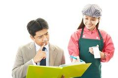 Waitress and customer. Waitress shows the menu to customer Stock Photos