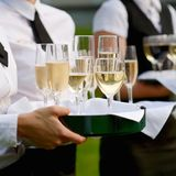 Waitress with dish of champagne glasses Royalty Free Stock Images