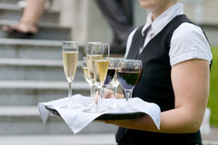 Waitress with dish of champagne glasses Stock Photography