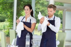 Waitress examining clean wine glass in restaurant Stock Images