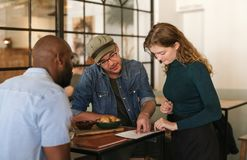 Waitress explaining the menu to customers in a bistro stock images