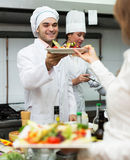 Waitress with food at kitchen Royalty Free Stock Photography
