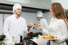 Waitress with food at kitchen Royalty Free Stock Images