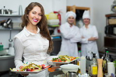 Waitress with food at kitchen Royalty Free Stock Photo