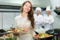Waitress with food at kitchen Stock Photography