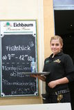 Waitress, Germany, standing by menu board.