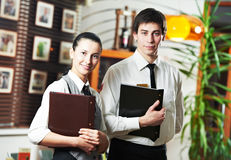 Waitress girl and waiter man. Waitress girl and waiter men of commercial restaurant in uniform waiting an order with menu royalty free stock photos