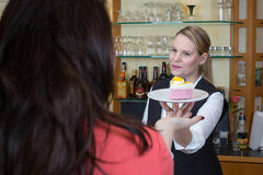 Waitress gives piece of cake to client Stock Photos