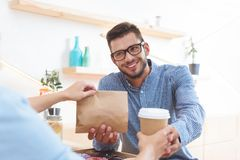 Waitress giving coffee to go and paper bag with take away food to smiling young client. In cafe stock photo