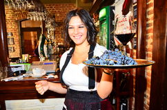 Waitress with grapes and wine leaving the bar Stock Images