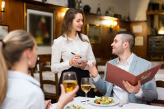 Waitress and guests in cafe. Young attractive waitress offering tasty dishes to guests couple. Focus on man Royalty Free Stock Images