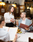 Waitress and guests in cafe. Young attractive waitress offering tasty dishes to smiling guests couple Stock Images