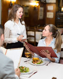 Waitress and guests in cafe Royalty Free Stock Images
