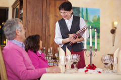 Waitress and guests in restaurant Stock Images