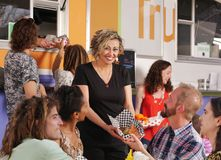 Waitress hands sandwich to customer. Seated beside food truck in the afternoon Royalty Free Stock Images