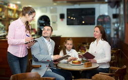 Waitress and happy family Royalty Free Stock Image